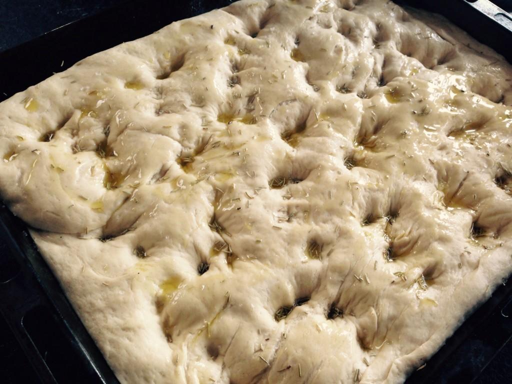 Efter hævning laves huller i dejen med knoerne. Der fordeles olie og krydderier på dejen.